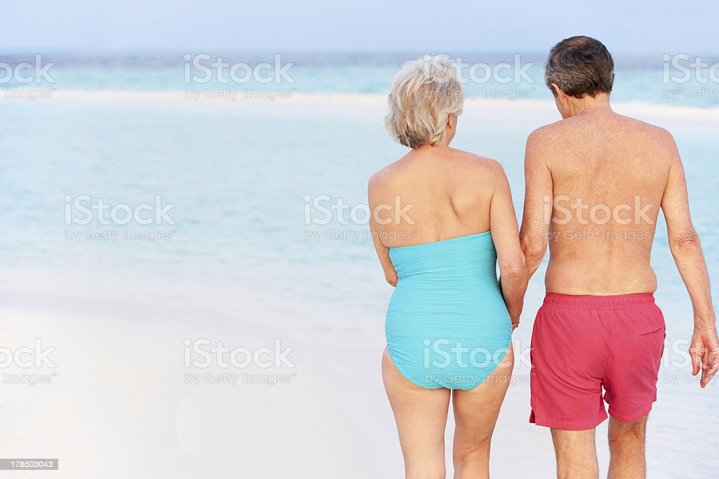 Rear View Of Senior Romantic Couple Walking In Tropical Sea royalty-free stock photo