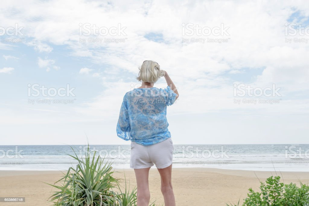 Rear view of senior woman on beach looking out to sea stock photo