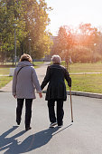 Rear view of senior woman walking with  assistent