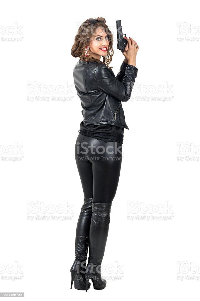 Rear view of sexy woman holding gun smiling at camera stock photo