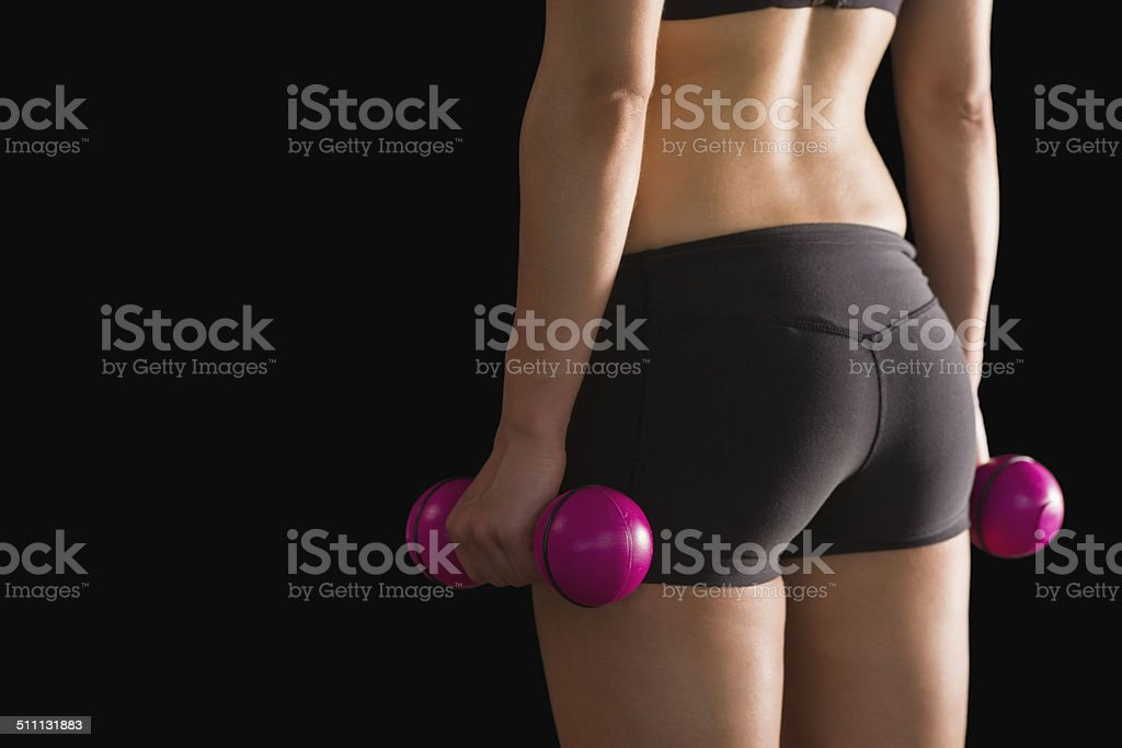 Rear view of slim woman wearing sportswear holding pink dumbbells stock photo