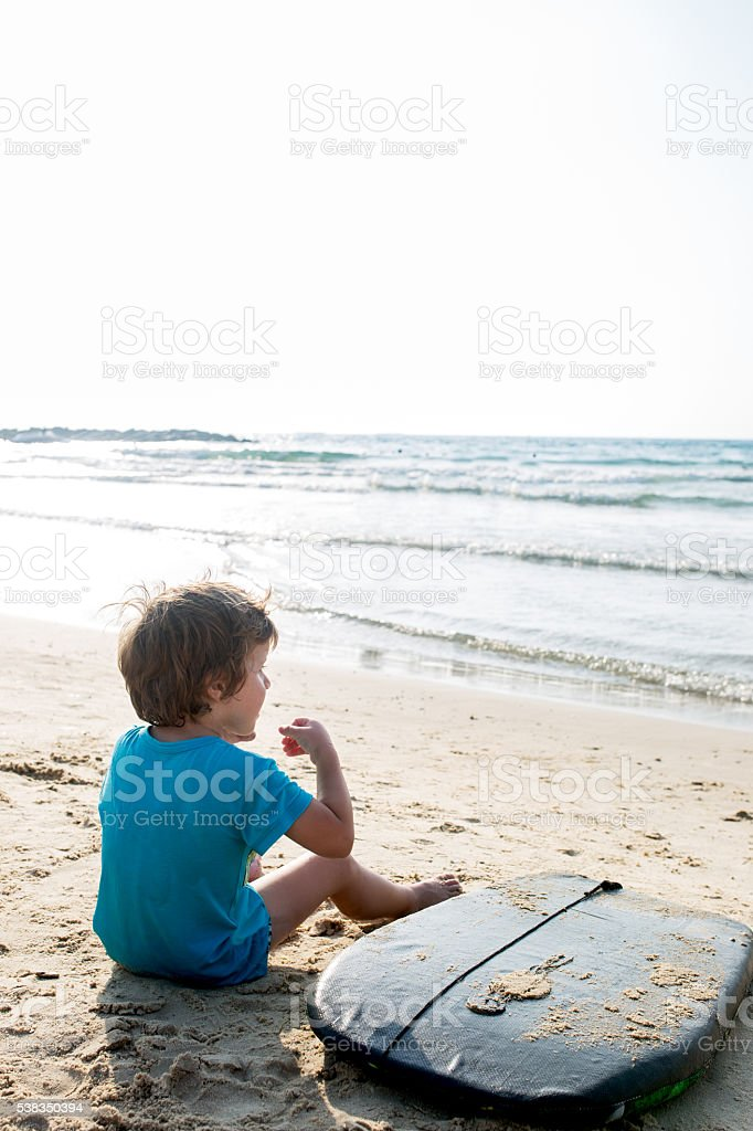 Rear view of small boy relaxing with surfboard on beach. stock photo