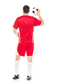 Rear view of soccer player holding ball