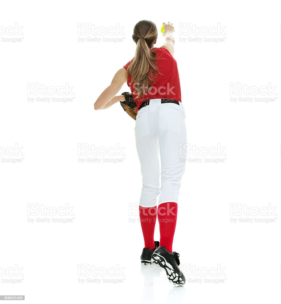 Rear view of softball player throwing a ball stock photo