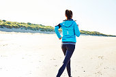 Rear view of sporty woman jogging on beach