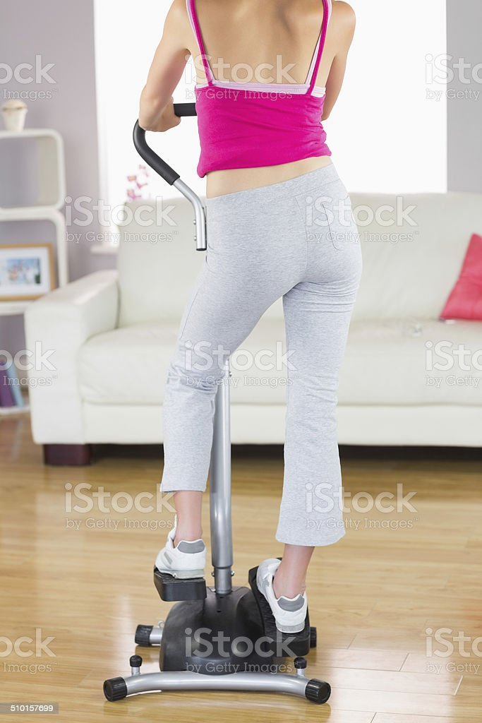 Rear view of sporty woman training on step machine stock photo