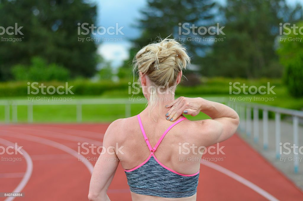 Rear view of sprinter massaging her own neck stock photo