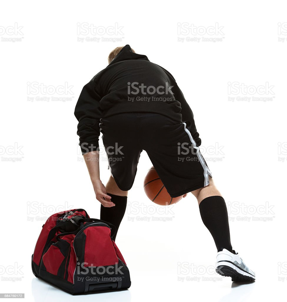 Rear view of student holding basketball stock photo