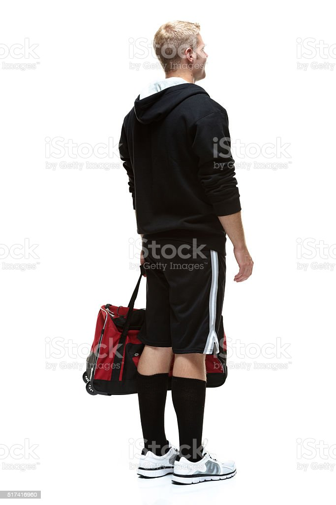 Rear view of student holding gym bag stock photo