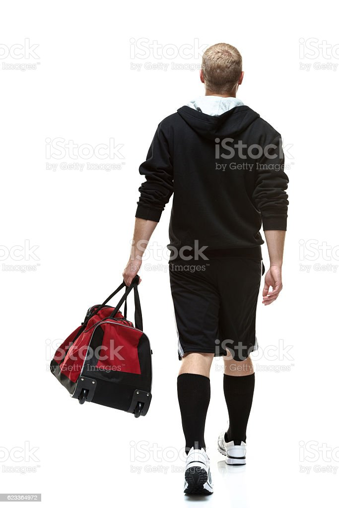 Rear view of student holding gym bag walking stock photo