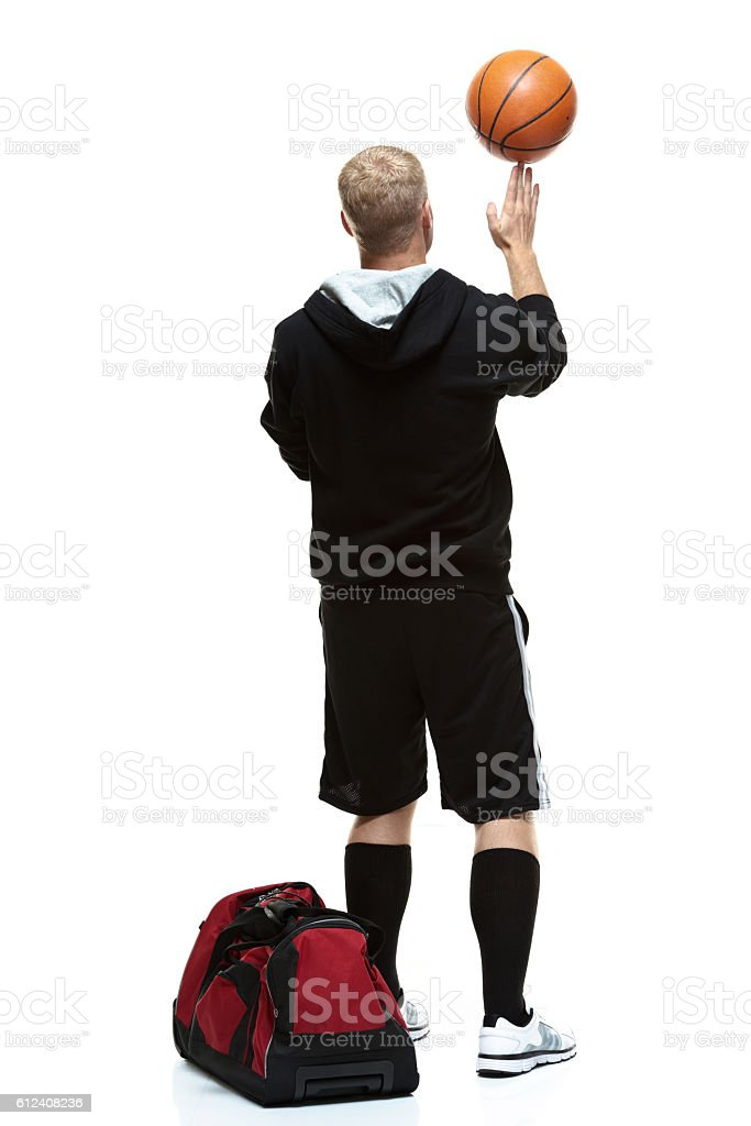 Rear view of student playing with basketball stock photo