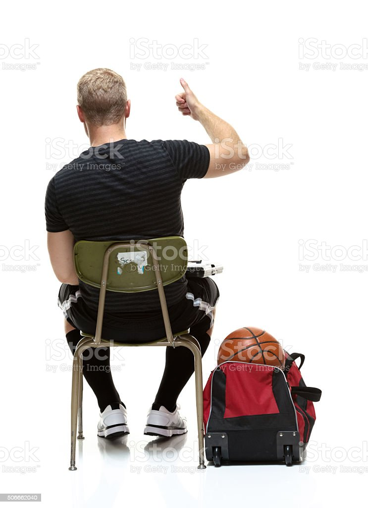 Rear view of student showing thumbs up stock photo