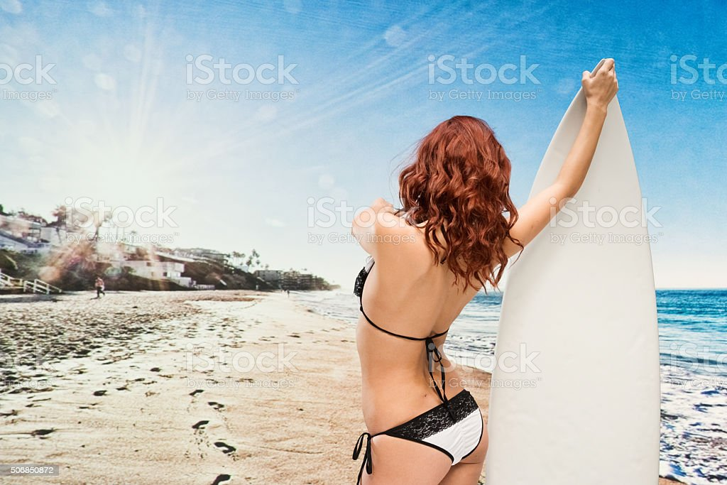 Rear view of surfer holding surfboard in the beach stock photo