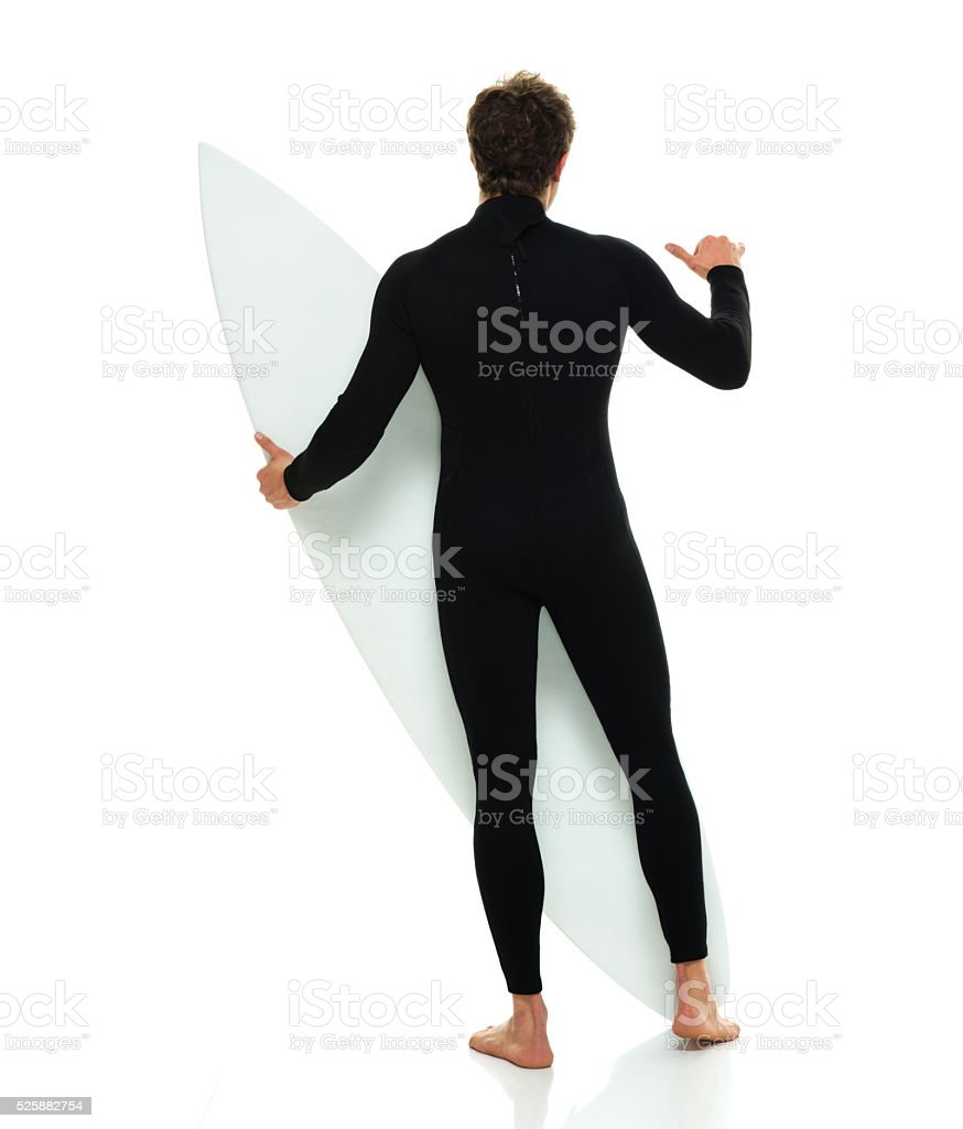 Rear view of surfer showing shaka sign stock photo