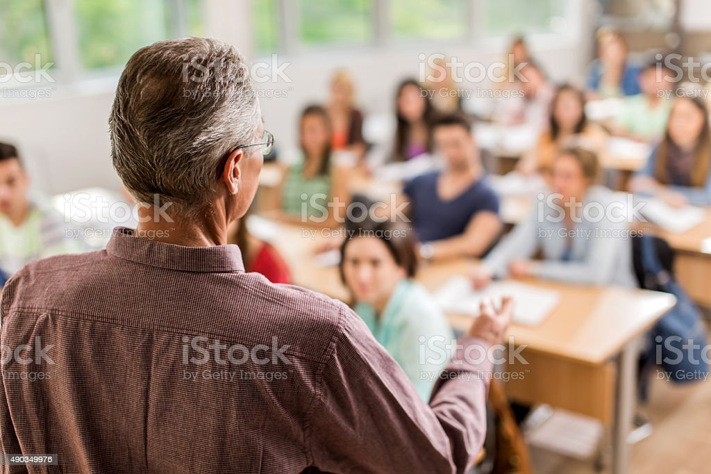 Rear view of teacher giving a lecture in the classroom. stock photo