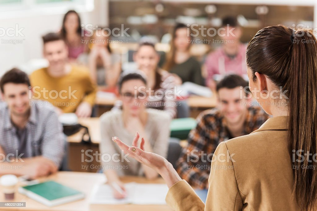 Rear view of teacher giving a lecture. stock photo