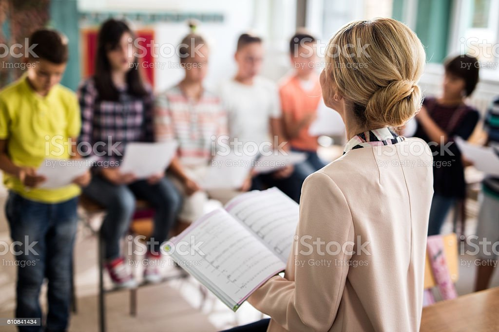 Rear view of teacher singing with children in the classroom. stock photo