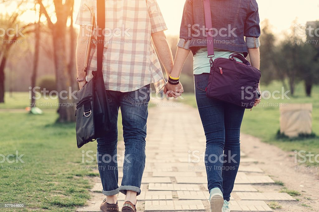 Rear view of teenage couple in the park stock photo
