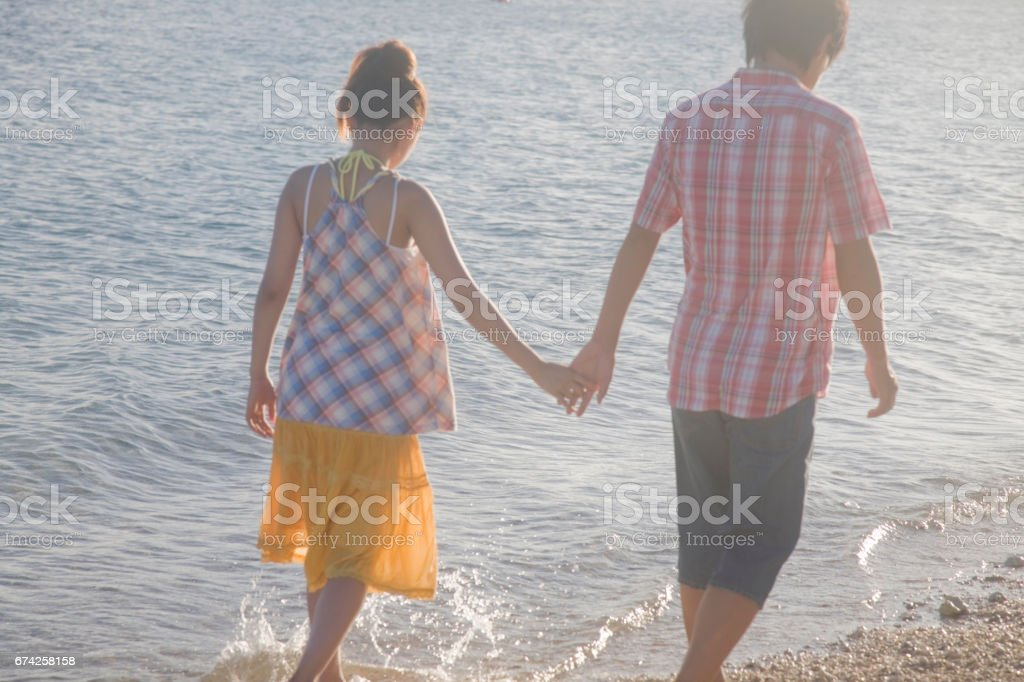 Rear view of the couples in the evening to join hands stock photo