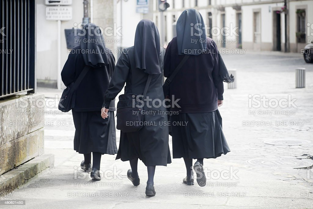 Rear view of three nuns walking in the street. stock photo