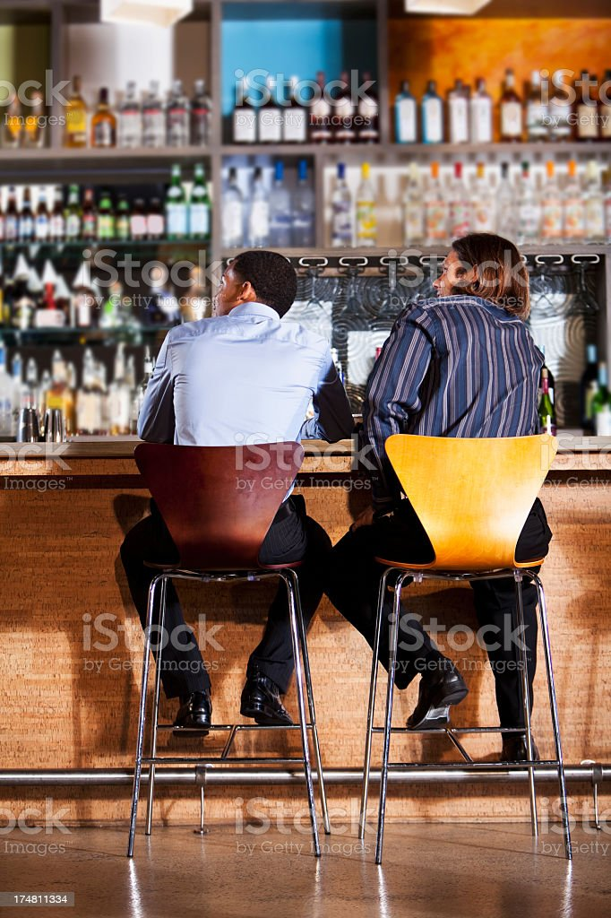 Rear view of two men at bar stock photo
