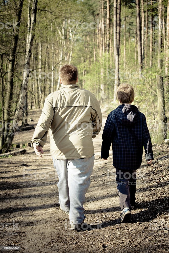 rear view of two overweight boys walk through the forest royalty-free stock photo