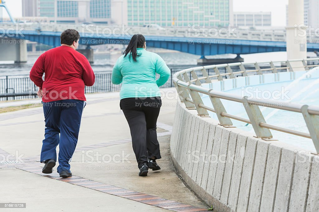 Rear view of two overweight people jogging stock photo