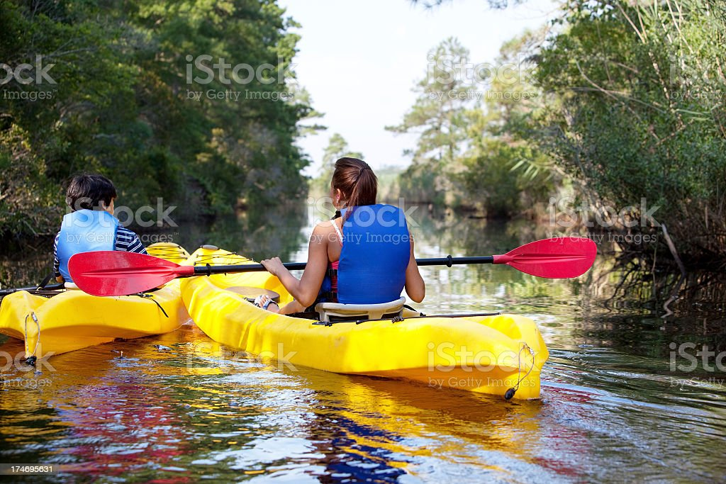 Rear view of two people kayaking in yellow boats and red oar royalty-free stock photo