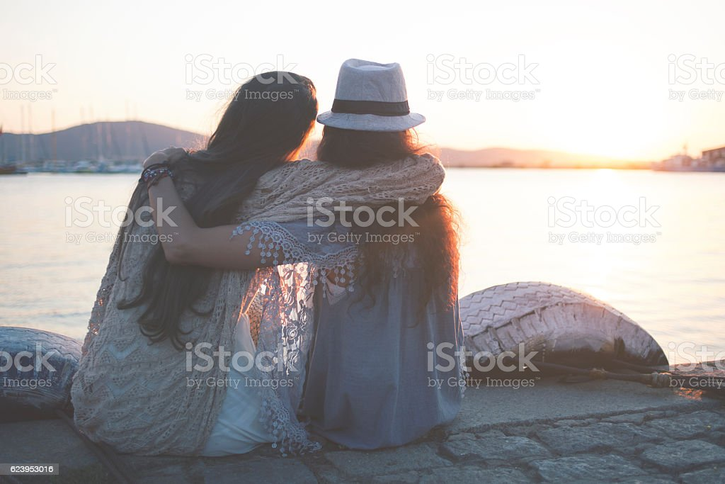 Rear view of two women watching the sunset stock photo