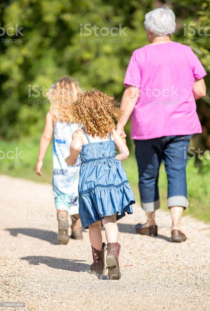 Rear View of Two Young Girls & Grandma Walking stock photo