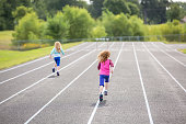 Rear View of Two Young Girls Running on Outdoor Track