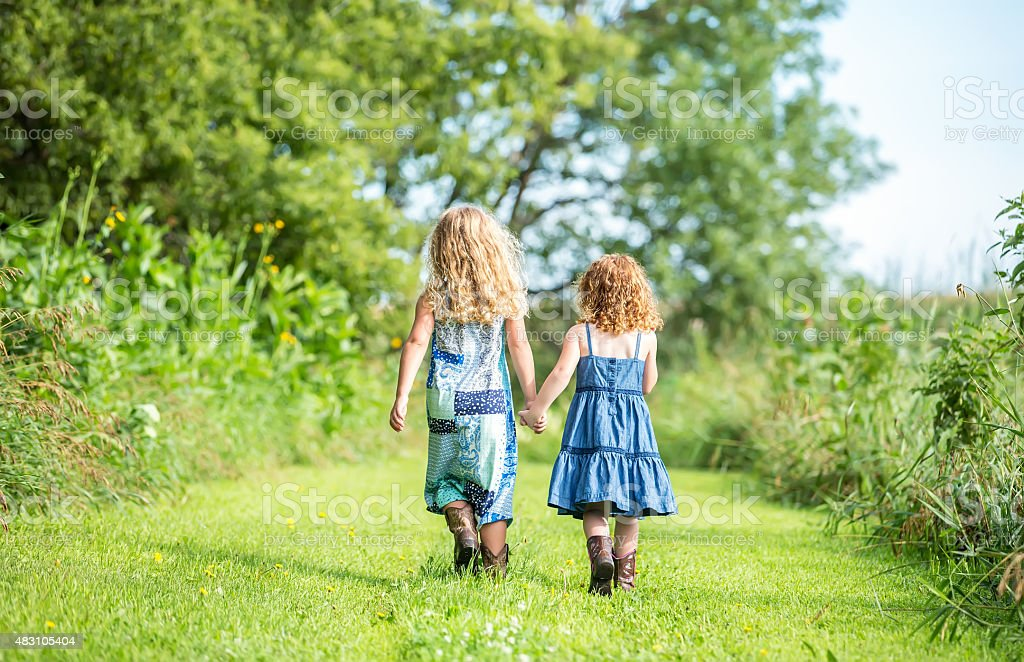 Rear View of Two Young Sisters Walking Holding Hands stock photo