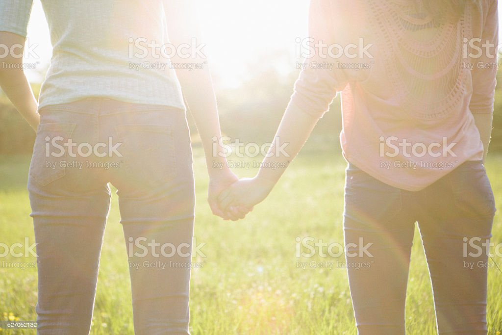 rear view of two young women holding hands, backlit stock photo