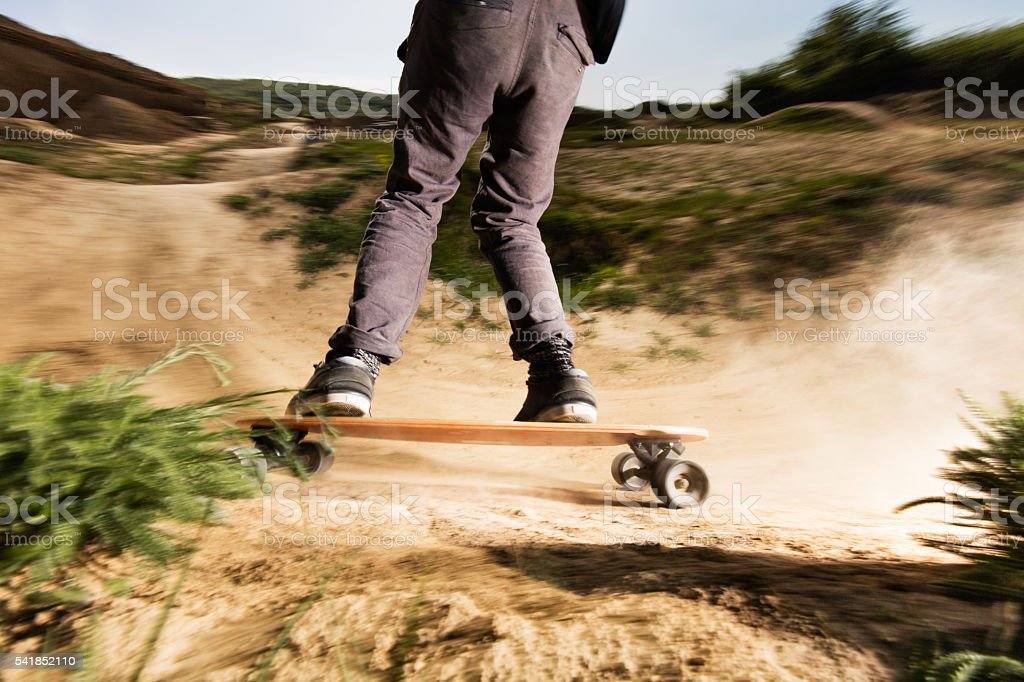 Rear view of unrecognizable man skateboarding on a dirt road. stock photo