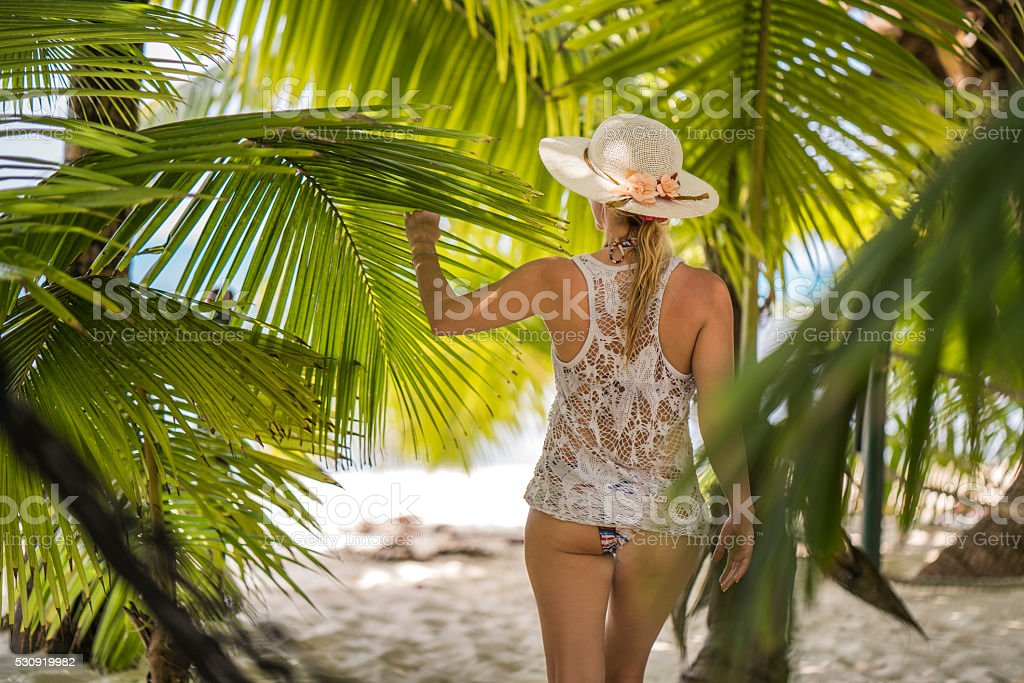 Rear view of woman among palm trees on the beach. stock photo