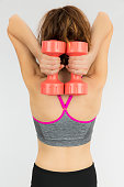 Rear view of woman holding dumbbells