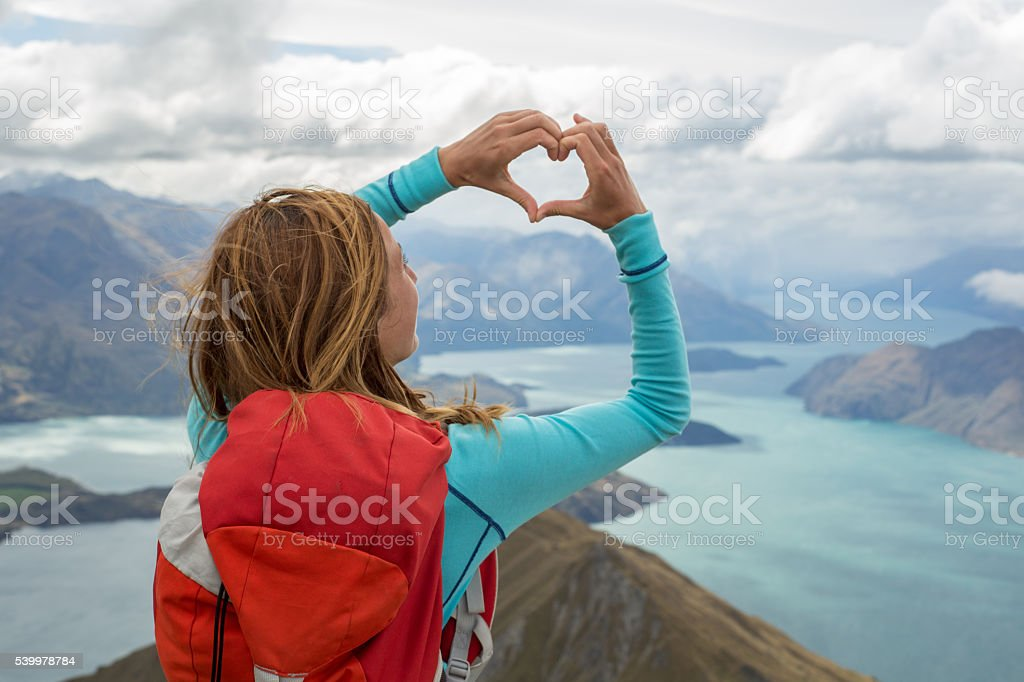 Rear view of woman making heart shape frame towards nature stock photo