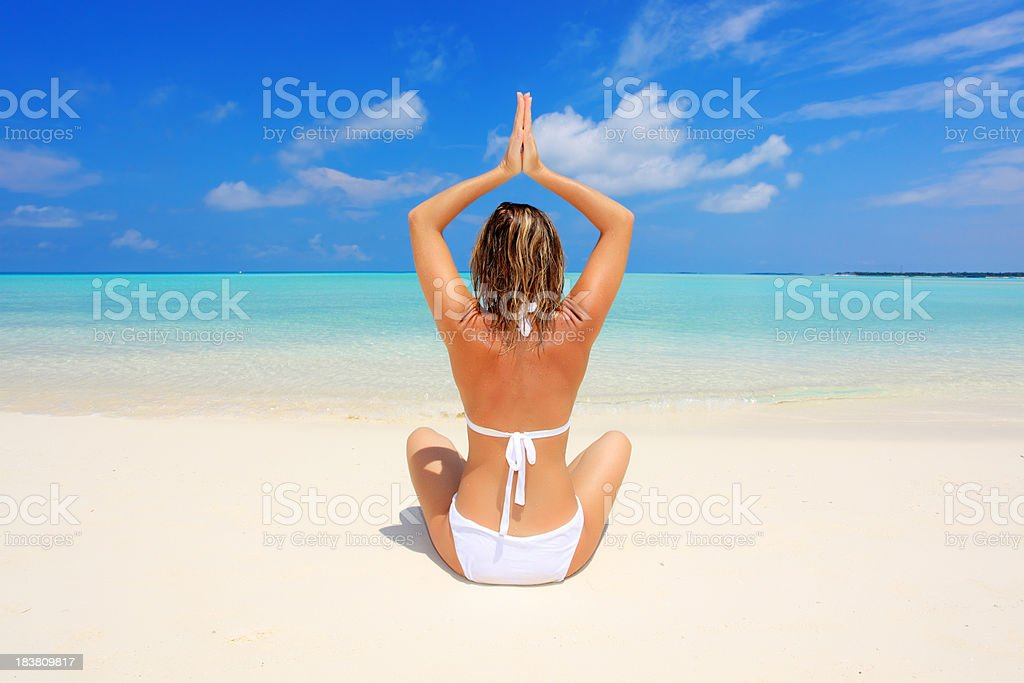 Rear view of woman meditating on the beach royalty-free stock photo