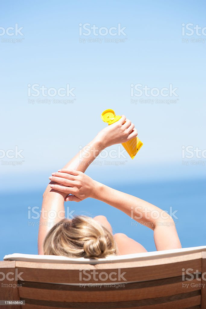 Rear view of woman on folding chair outdoors applying sunblock stock photo