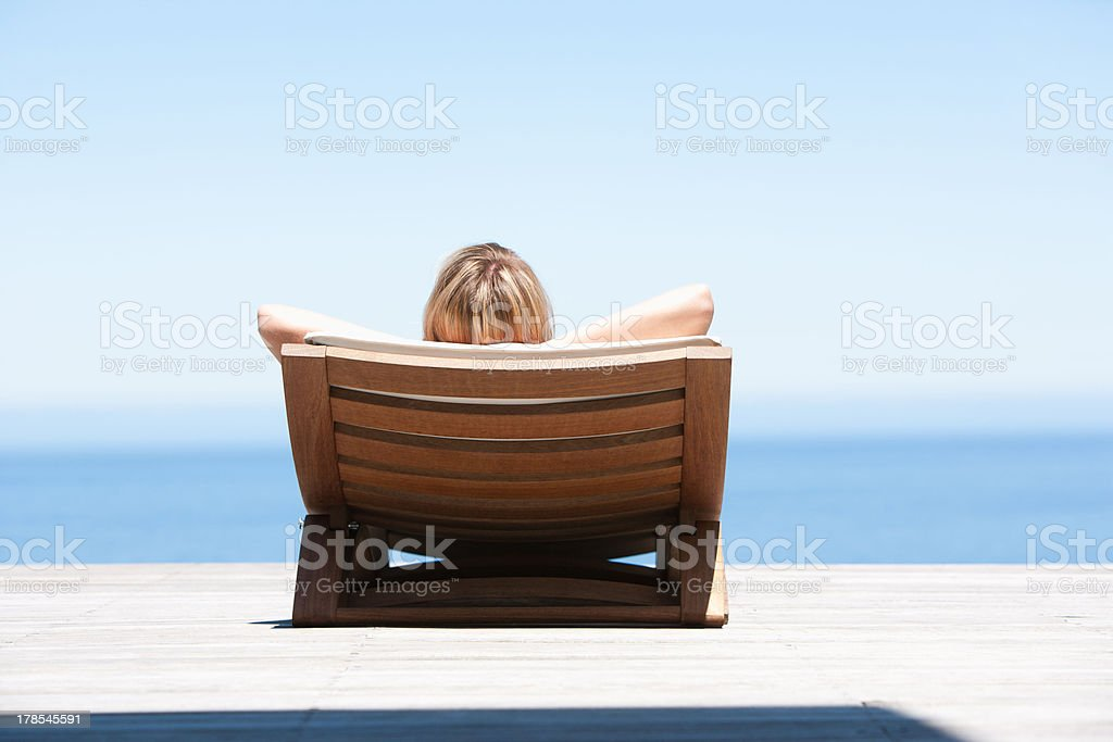 Rear view of woman reclining on folding chair outdoors stock photo