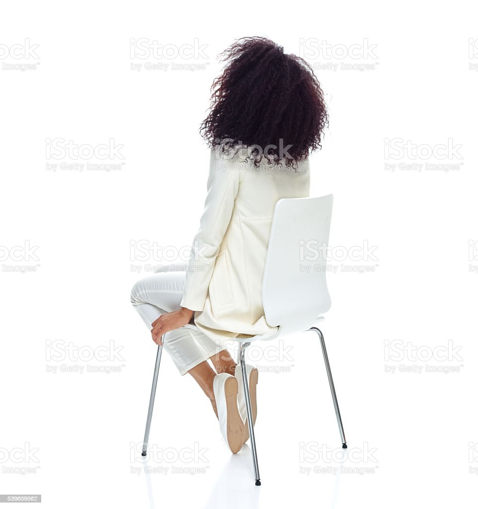 Rear view of woman sitting on chair and looking up stock photo