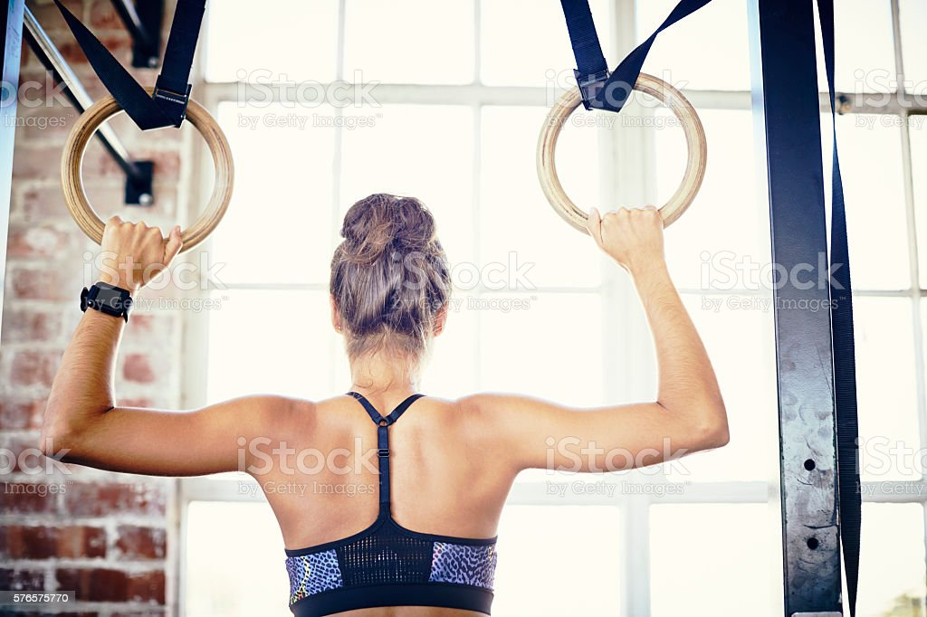 Rear view of woman training on gymnastic rings stock photo