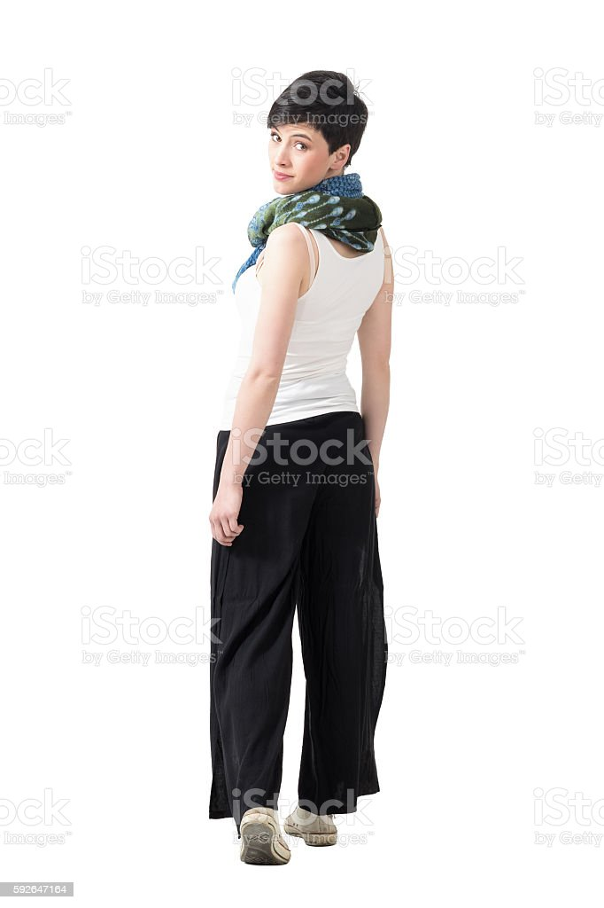 Rear view of woman walking away turning head at camera stock photo