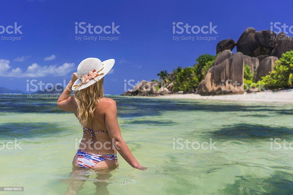 Rear view of woman walking through sea on Seychelles. stock photo