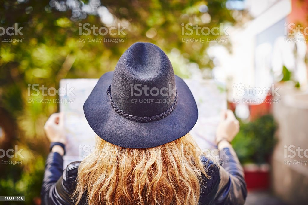 Rear view of woman wearing hat while holding city map stock photo