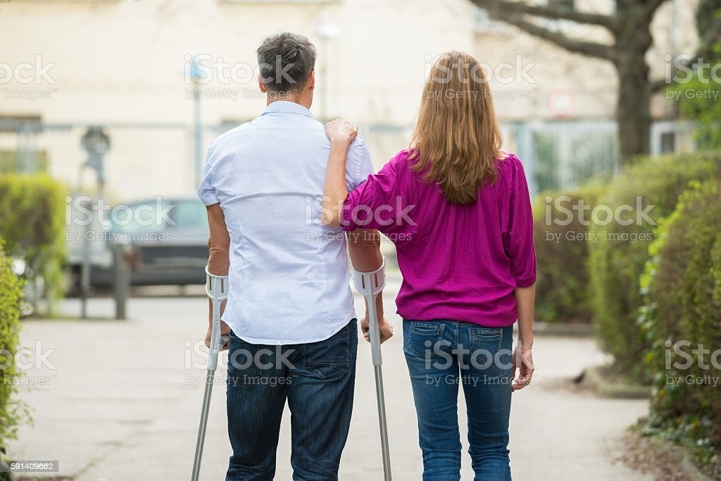 Rear View Of Woman With Her Disabled Husband stock photo