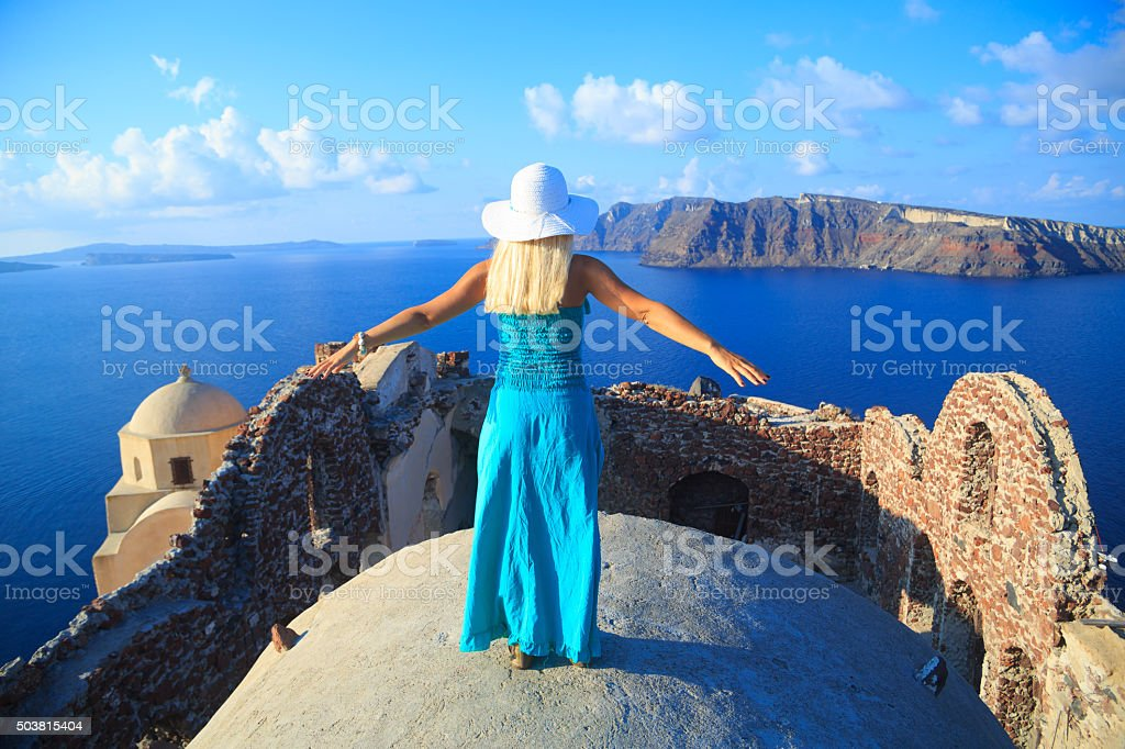 Rear view of Woman with turquoise dress in Santorini, Greece. stock photo