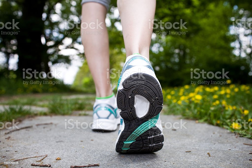 Rear view of woman's shoes walking cross country on a trail stock photo