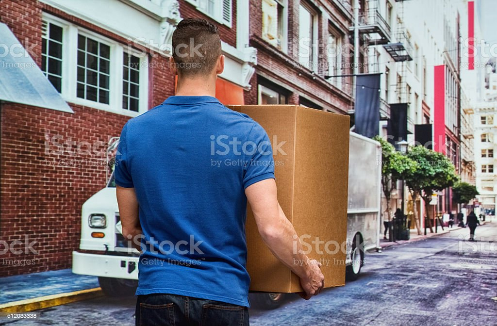 Rear view of worker holding box outdoor stock photo