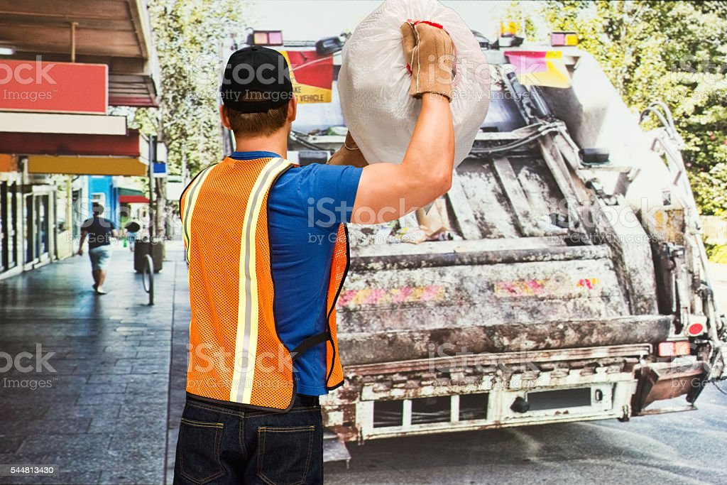 Rear view of worker holding garbage bag stock photo